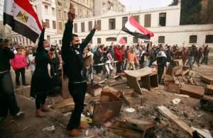 Protesters gesture as they clash with security forces near the Interior Ministry in Cairo