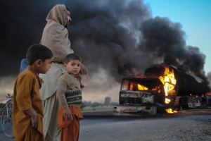 Boys stand next to a man as they watch fuel trucks which were set ablaze in the Bolan district of Pakistan's Baluchistan province